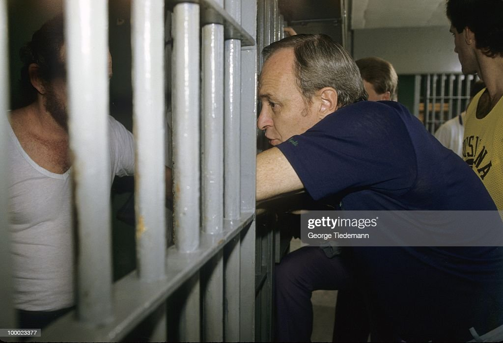 LSU coach Dale Brown leaning against prison bars at Louisiana State Penitentiary chatting with inmate on death row. Angola, LA 9/20/1985