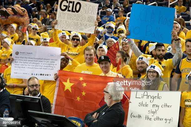 Michigan fans in stands with signs that read UCLA HAS NO BALLS and GELO STOLE MY BEARD AND FLED OVERSEAS during game vs UCLA at Crisler Center Ann...