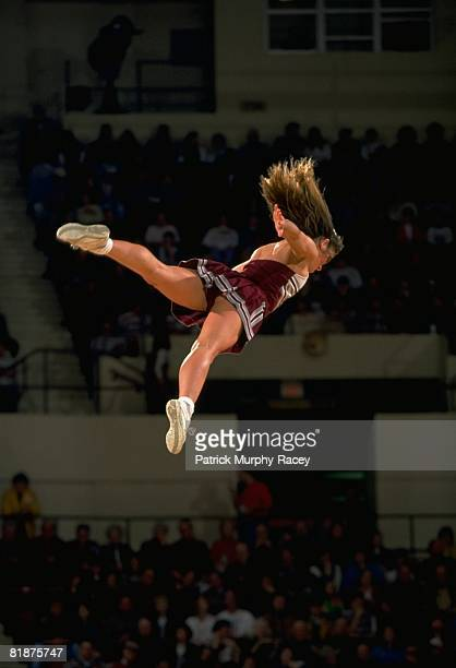 College Basketball: Mississippi State cheerleader in action, flying through air during game vs Kentucky, Starkville, MS 1/22/1994