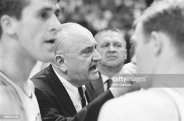 NCAA Final Four Closeup of Kentucky coach Adolph Rupp on sidelines with players during game vs Texas Western at Cole Field House College Park MD...