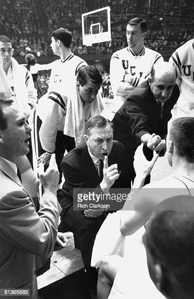 College Basketball NCAA Final Four UCLA coach John Wooden in huddle with team during timeout of game vs Duke Assistant coach handing out lemons...