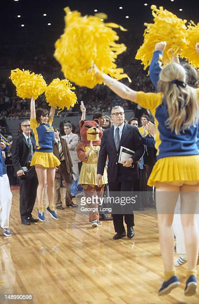 NCAA Final Four UCLA coach John Wooden on court walking past cheerleaders before game vs Flordia State at Los Angeles Memorial Sports Arena Los...
