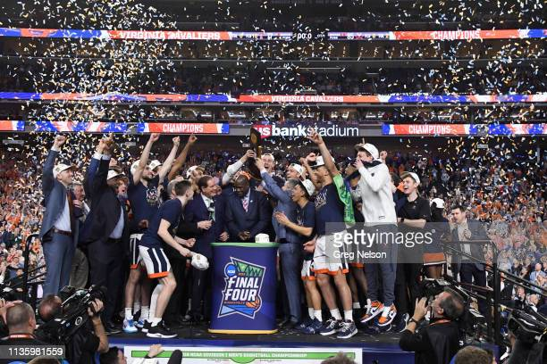NCAA Finals Virginia coach Tony Bennett holding up NCAA National Championship trophy with players victoriious on stage with and with CBS announcer...