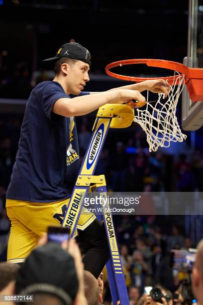 NCAA Playoffs Michigan Duncan Robinson on ladder cutting net after winning game vs Florida State at Staples Center Los Angeles CA CREDIT John W...