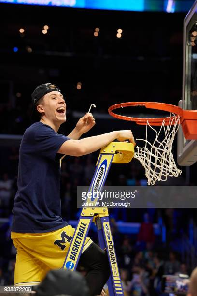 NCAA Playoffs Michigan Duncan Robinson victorious on ladder after cutting net after winning game vs Florida State at Staples Center Los Angeles CA...