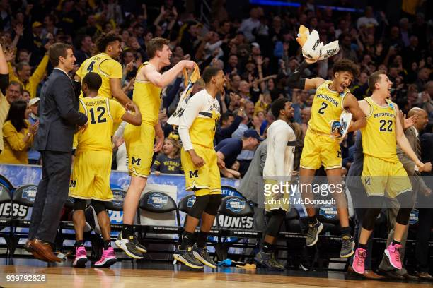 NCAA Playoffs Michigan Jordan Poole Duncan Robinson and teammates victorious on sidelines bench during game vs Texas AM at Staples Center Los Angeles...
