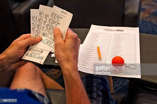 NCAA Playoffs View of sports book patron holding betting slips while watching March Madness games at Terribles Hotel Casino Las Vegas NV CREDIT Chris...