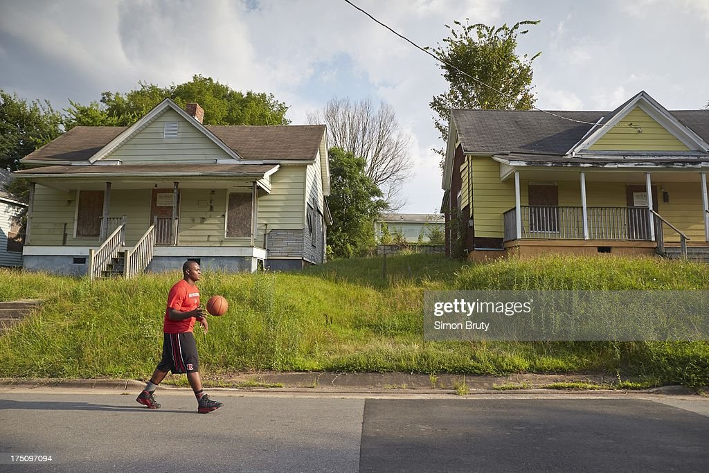Portrait of former UNC-Wilmington player Tyree Graham walking by his childhood home on Piedmont Avenue. Graham, who has played at multiple colleges and high schools during his career, represents the high frequency of transfers over the last seven seasons. Simon Bruty F380 )