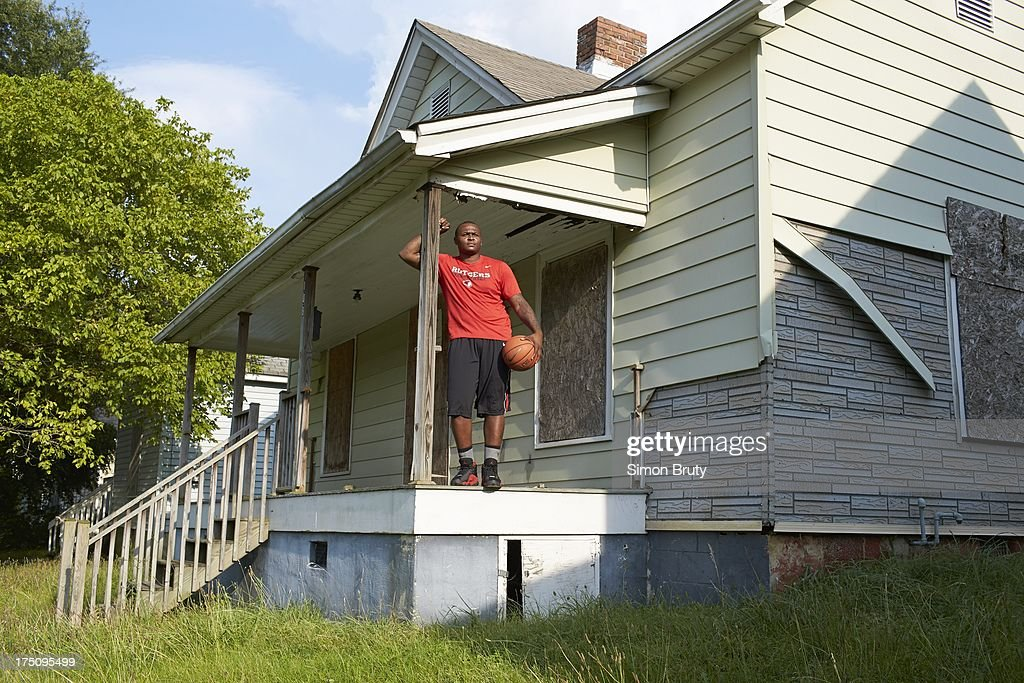 Portrait of former UNC-Wilmington player Tyree Graham in front of his childhood home on Piedmont Avenue. Graham, who has played at multiple colleges and high schools during his career, represents the high frequency of transfers over the last seven seasons. Simon Bruty F104 )