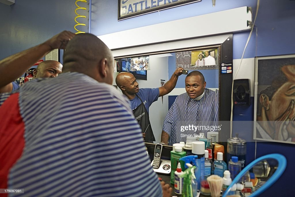 Portrait of former UNC-Wilmington player Tyree Graham getting his hair cut by Len Lilly at Forty Below Barber Shop. Graham, who has played at multiple colleges and high schools during his career, represents the high frequency of transfers over the last seven seasons. Simon Bruty F124 )