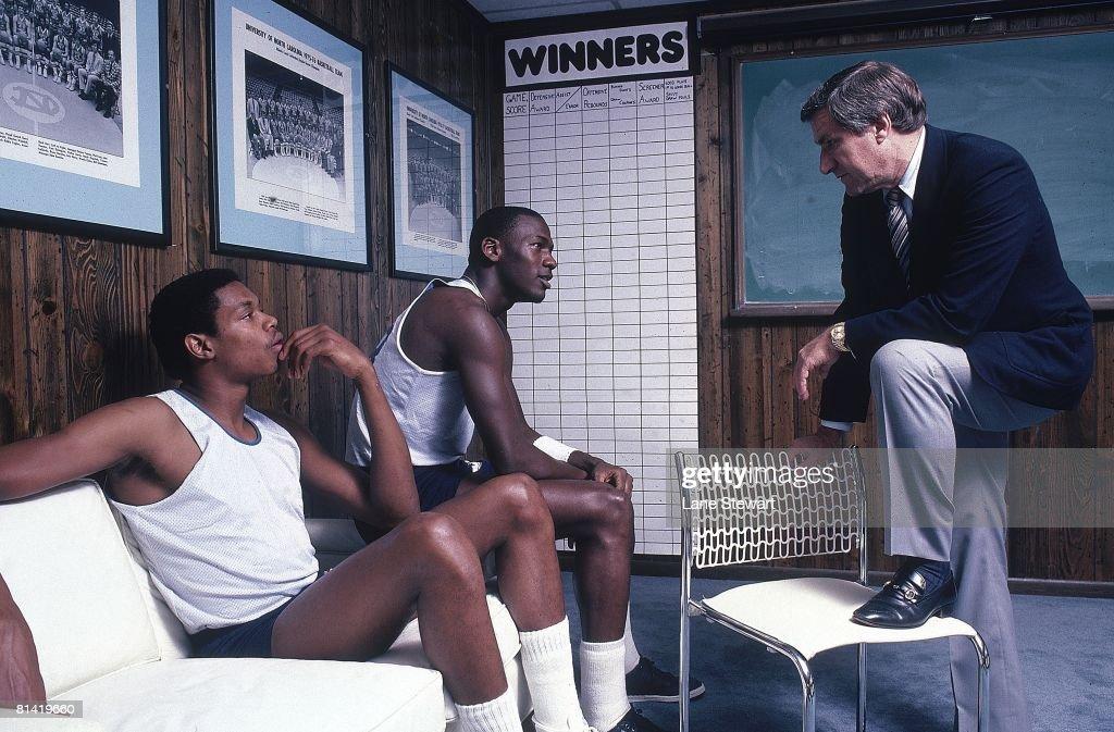 Portrait of North Carolina Sam Perkins (41), Michael Jordan (23), and coach Dean Smith in office at University of North Carolina, Chapel Hill, NC