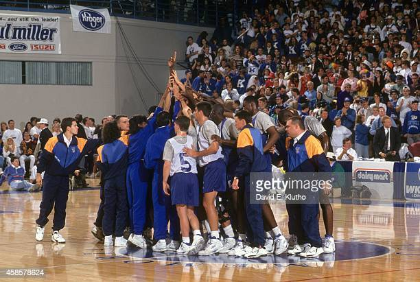 View of Kentucky players and coaches victorious in huddle after Midnight Madness practice at Rupp Arena View of assistant coach Bernadette Locke...