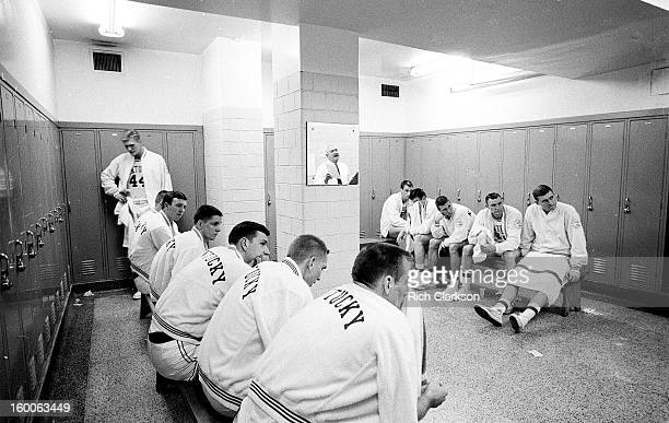 View of Kentucky players listening to coach Adolph Rupp in locker room before game vs Mississippi at Memorial Coliseum View of Rupp's reflection in...