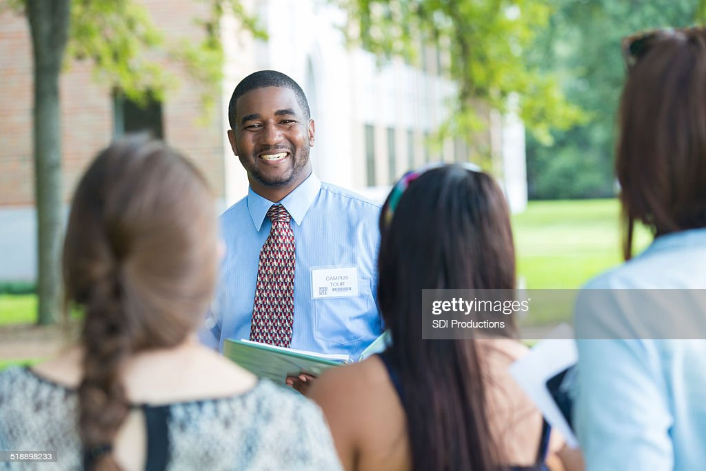 College campus tour guide talking with prospective students outdoors : Stock Photo