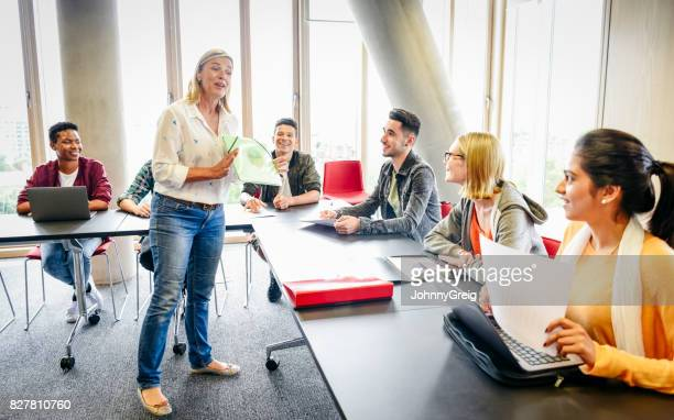 college classroom with mature female teacher and young multi ethnic students - adult stock pictures, royalty-free photos & images