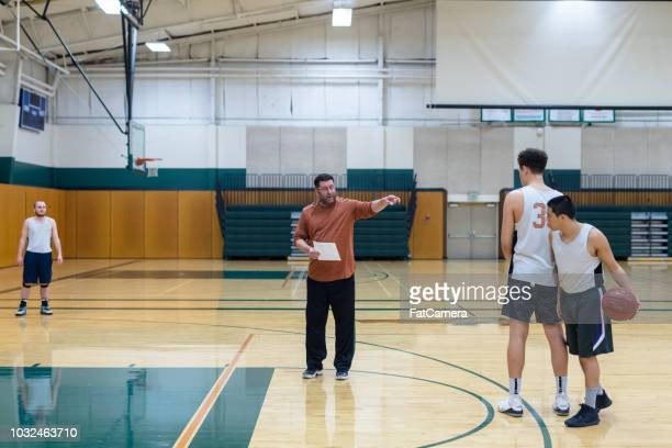 College coach running men's basketball practice