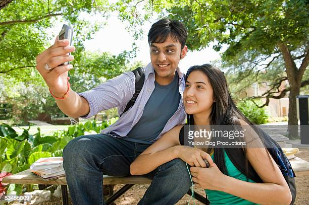 college  coeds taking cell phone photo  - indian college girls stockfoto's en -beelden
