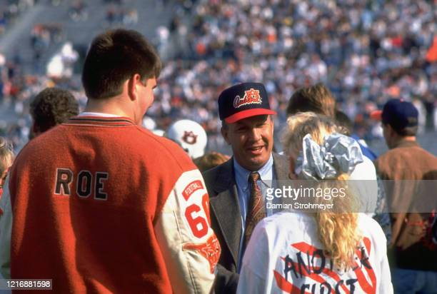 Auburn coach Pat Dye with recruit and his hostess on field before game vs Florida at JordanHare Stadium Auburn AL CREDIT Damian Strohmeyer