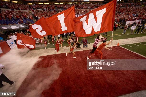 Big 10 Championship Wisconsin cheerleaders taking field carrying flags that spell out WISCONSIN with mascot Bucky Badger before game vs Ohio State at...