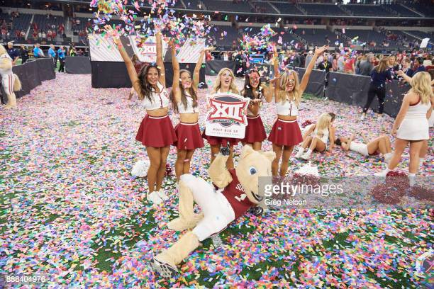 Big 12 Championship Oklahoma cheerleaders tossing confetti up in air and holding BIG 12 sign with mascot laying down on field after game vs Texas...