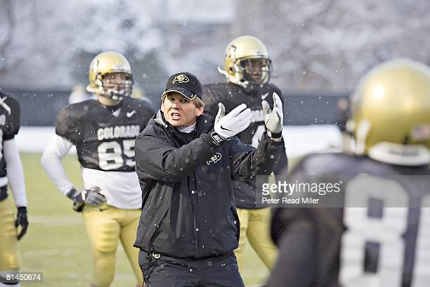 College Football Colorado head coach Dan Hawkins giving instructions to team during spring practice Snow weather Boulder CO 3/21/2006