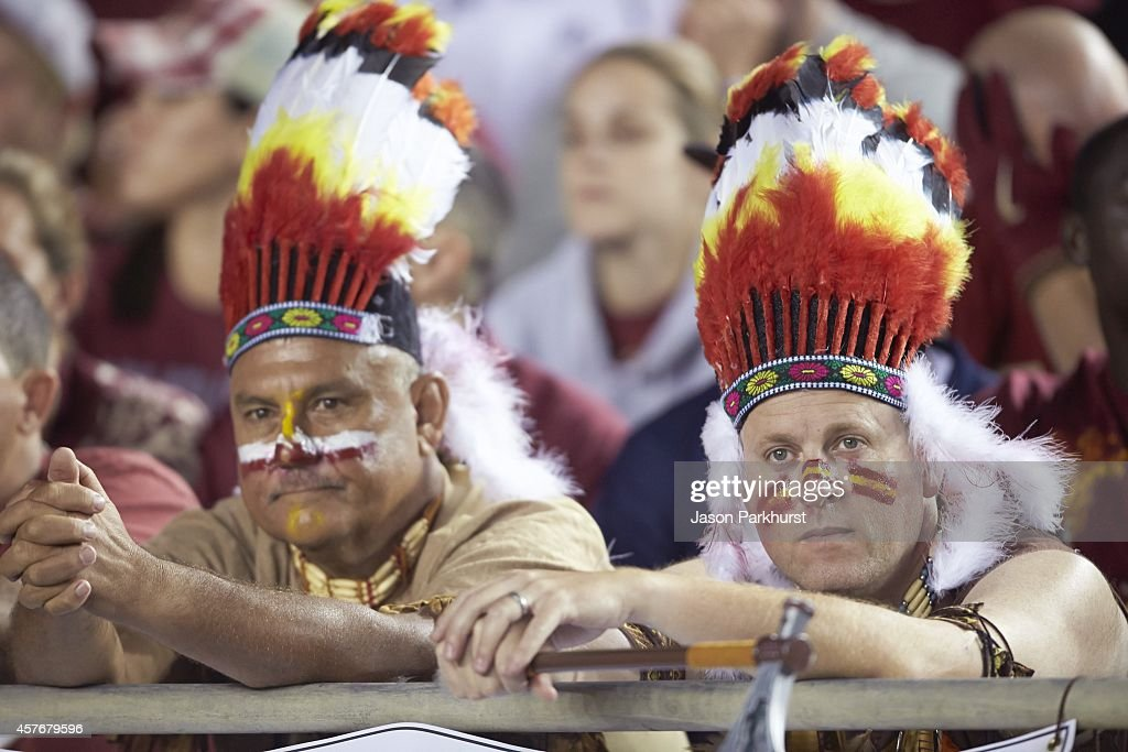 Florida State Fans With Face Paint And Feather Headdress In School Colors Stands During