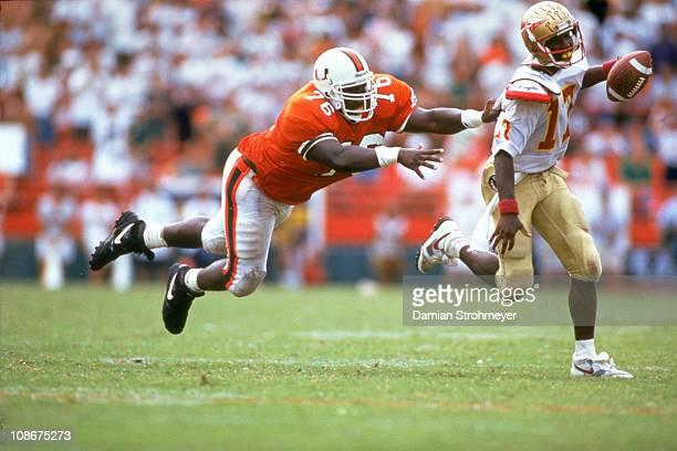 Florida State QB Charlie Ward in action under pressure vs Miami Warren Sapp at Orange Bowl StadiumMiami FL 10/3/1992CREDIT Damian Strohmeyer