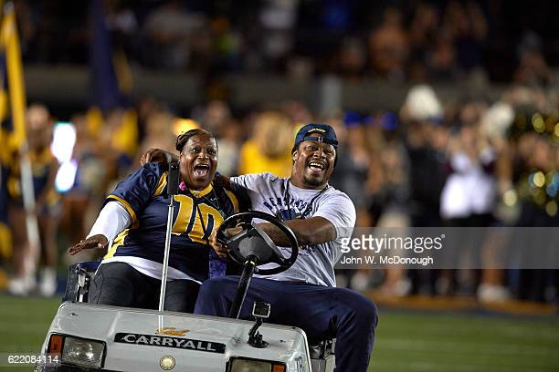 Former California running back Marshawn Lynch with his mother Delisa driving a golf cart on field and leading California players onto field before...