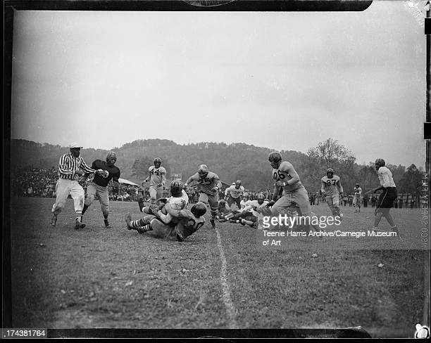 College football game with Johnson C Smith Joe Williams tackling West Virginia State Bacon Smith in foreground and referee on left West Virginia...
