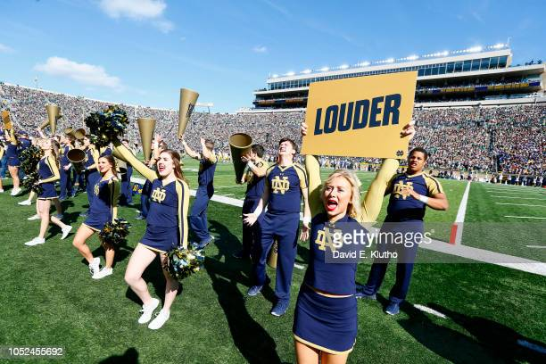 Notre Dame cheerleaders performing on field during game vs Pittsburgh at Notre Dame Stadium Cheerleader holding up sign that reads LOUDER Notre Dame...
