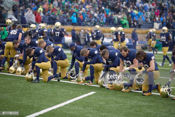 Notre Dame players down on one knee praying before game vs Wake Forest at Notre Dame Stadium South Bend IN CREDIT David E Klutho