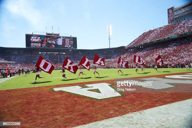 Oklahoma cheerleaders on field with flags that spell out OKLAHOMA during game vs Iowa State at Gaylord Family Oklahoma Memorial Stadium Norman OK...