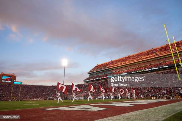 Oklahoma cheerleaders taking field with flags spelling out OKLAHOMA during game vs West Virginia at Gaylord Family Oklahoma Memorial Stadium Norman...