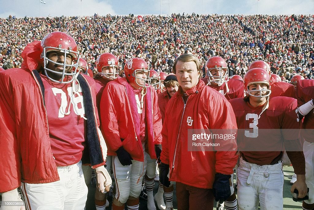 Oklahoma coach Barry Switzer on sidelines with players before game vs Oklahoma State. Norman, OK
