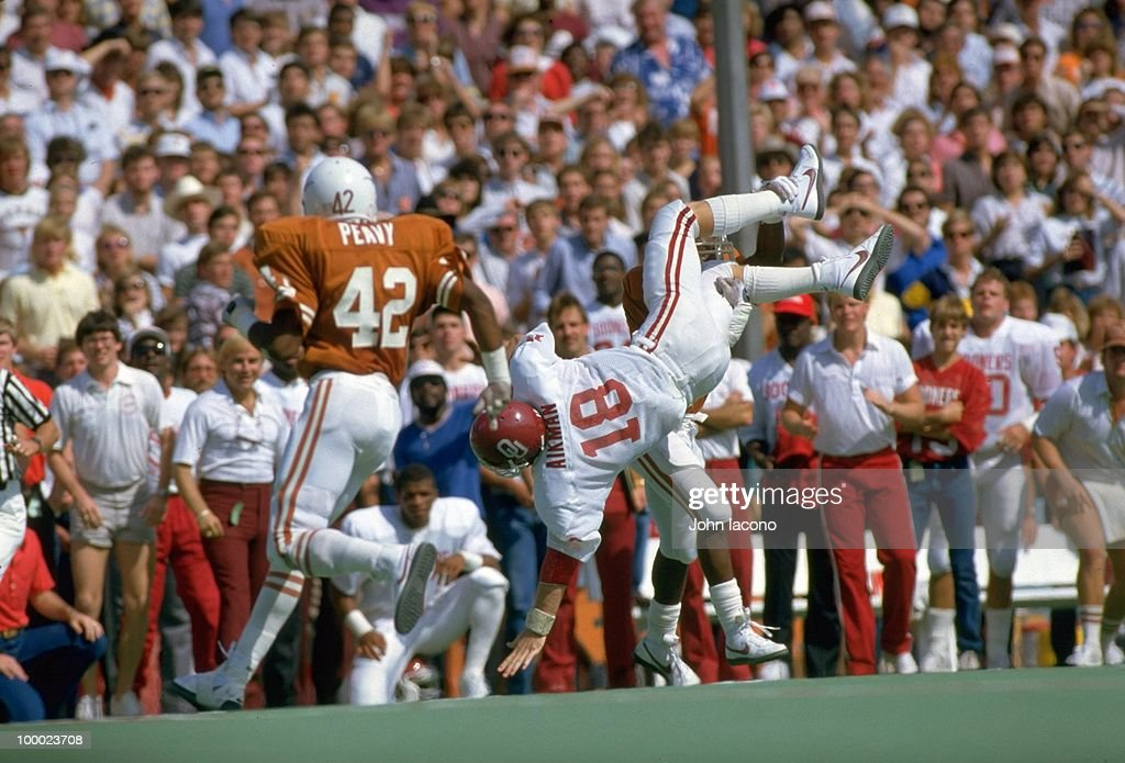 Oklahoma QB Troy Aikman (18) in action, getting upended vs Texas. Dallas, TX