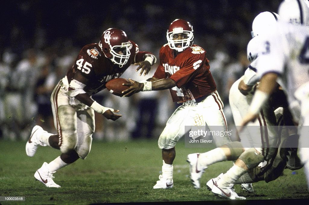 Oklahoma QB Jamelle Holieway (4) in action, handoff to teammate Lydell Carr (45) vs Penn State. Miami, FL 1/1/1986