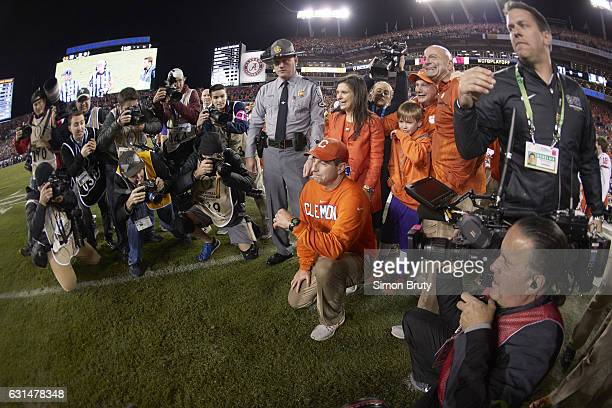 Playoff National Championship Clemson coach Dabo Swinney victorious down on one knee with wife Kathleen after winning game vs Alabama at Raymond...