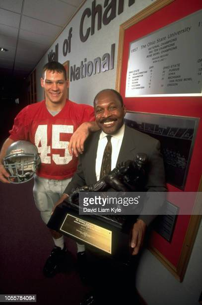 Portrait of Ohio State Andy Katzenmoyer and former Heisman winner Archie Griffin holding his Heisman trophy in front of the Wall of Champions on...