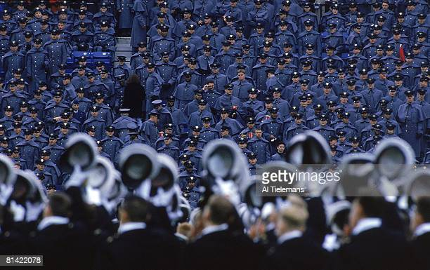 College Football Rear view of Navy Midshipmen sailors doffing caps in direction of Army Cadets soldiers in stands at Veterans Stadium before Army vs...