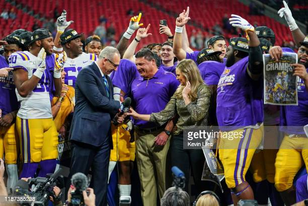 SEC Championship Game LSU coach Ed Orgeron victorious shaking hands with SEC commissioner Greg Sankey during interview on field with CBS sideline...