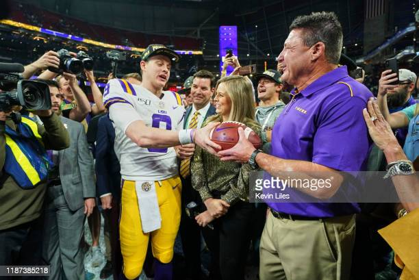 Championship Game: LSU QB Joe Burrow handing over game ball to coach Ed Orgeron during interview on field with CBS sideline reporter Jamie Erdahl...