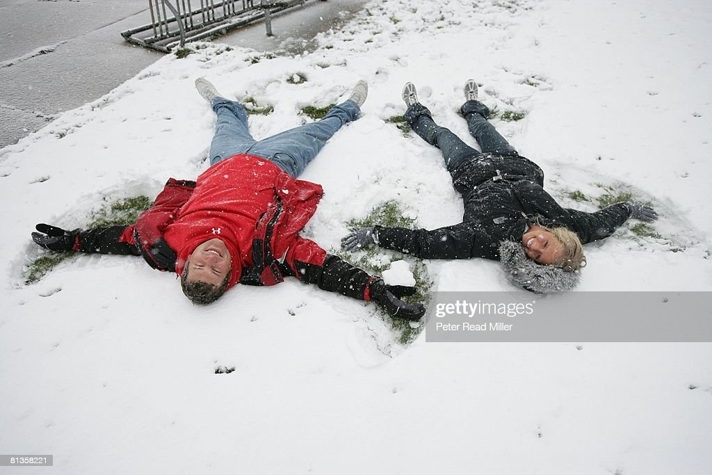 Unusual casual portrait of Wisconsin Joe Thomas making snow angel with fiancee Annie Nelson at off-campus house, Madison, WI 4/11/2007
