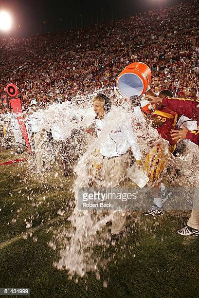 College Football: USC victorious, pouring Gatorade water bucket on coach Pete Carroll after winning game vs UCLA, Los Angeles, CA 12/3/2005