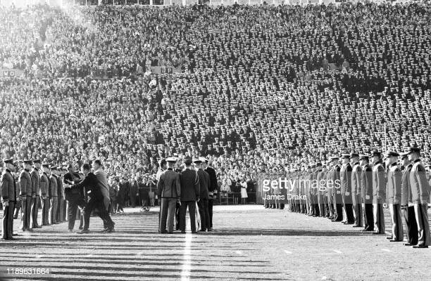View of fan getting pushed away by SSA during coin toss by United States President John F Kennedy before Army vs Navy game at Municipal Stadium...