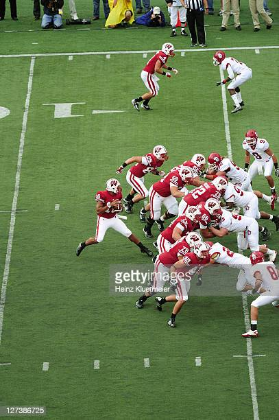 Wisconsin QB Russell Wilson in action, dropping back behind offensive line Ricky Wagner , Travis Frederick , Peter Konz , Kevin Zeitler , and Rob...