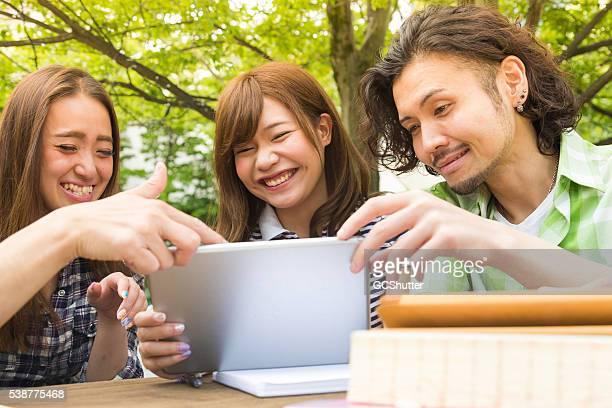Collège amis s'amusant avec leur tablette numérique