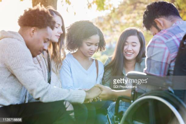college friends praying together - praying stock pictures, royalty-free photos & images