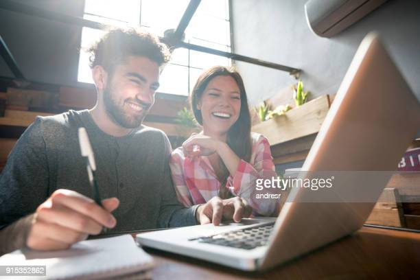 College friends studying at a coffee shop looking at a laptop laughing and having fun