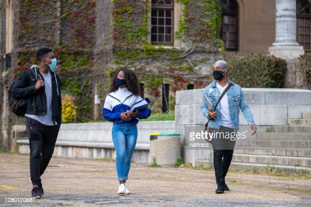 college friends walking together wearing protective face masks - small group of people stock pictures, royalty-free photos & images