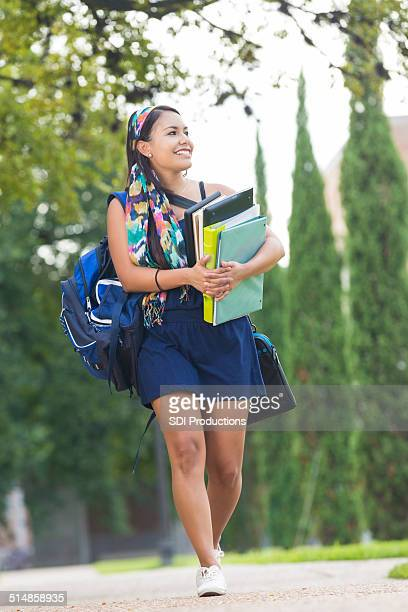 College girl carrying books to class on beautiful campus